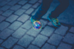 Man walking on urban street with soap bubble floating by