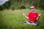 Meditating kid in sunglasses
