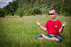 Meditating kid in sunglasses