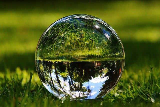Glass ball on grass, mirroring the scenery around