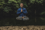 Man sitting in meditation posture floating off the group