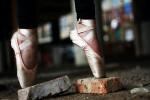 Ballet dancer balanced en pointe on broken concrete