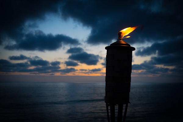 Fire torch against the sea and sky at nightfall