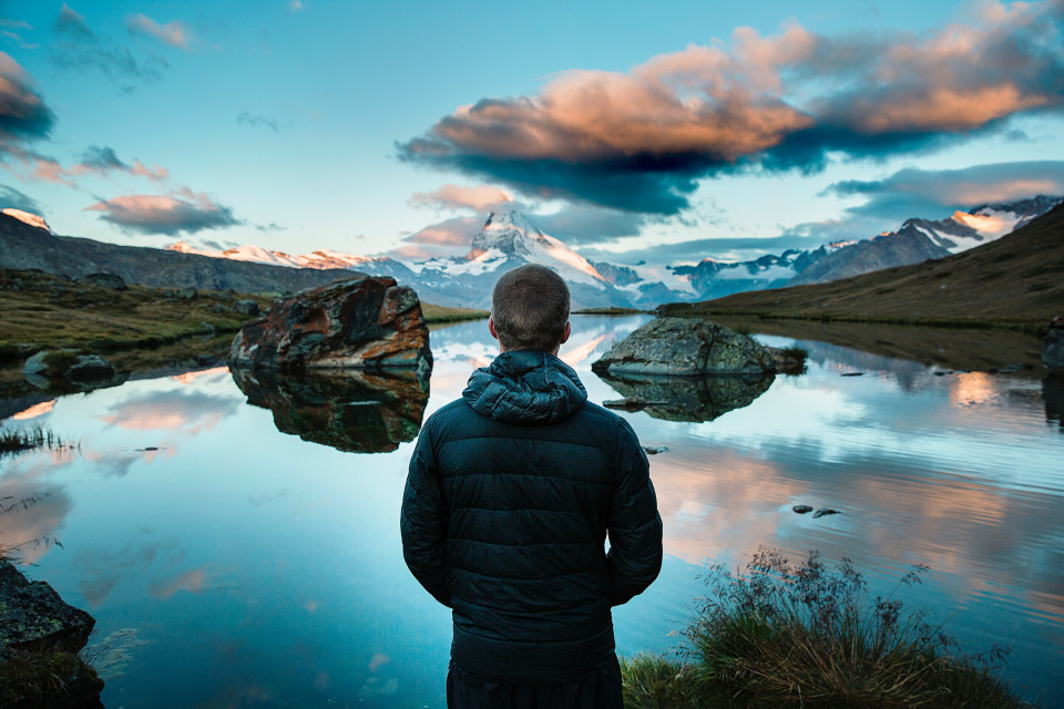 Man standing in front of still, reflective lake in the mountains.