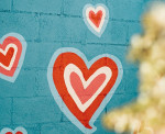Hearts painted on a blue brick wall