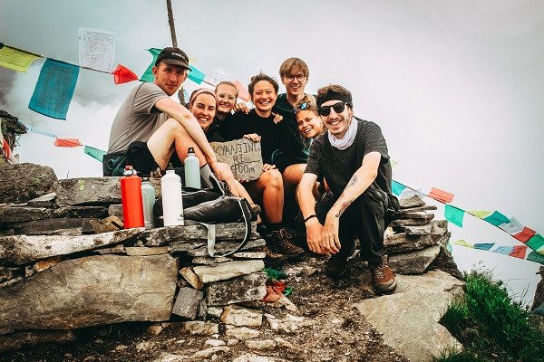 Friends sitting on a hilltop with Buddhist prayer flags behind them