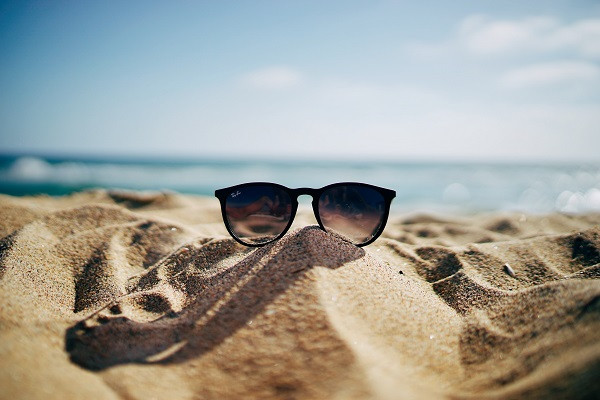 Sunglasses on a sand dune through which you can see the ocean and blue sky