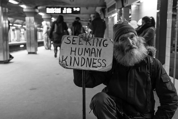 Man holding a sign saying seeking human kindness