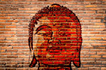 Buddha head painted on a brick wall