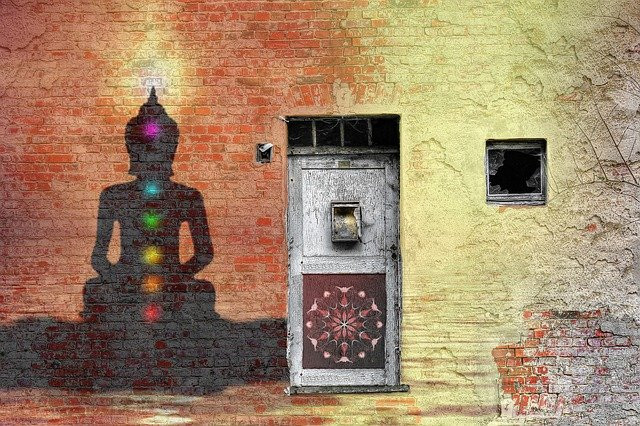 Buddha outline on brick wall with coloured chakra centres