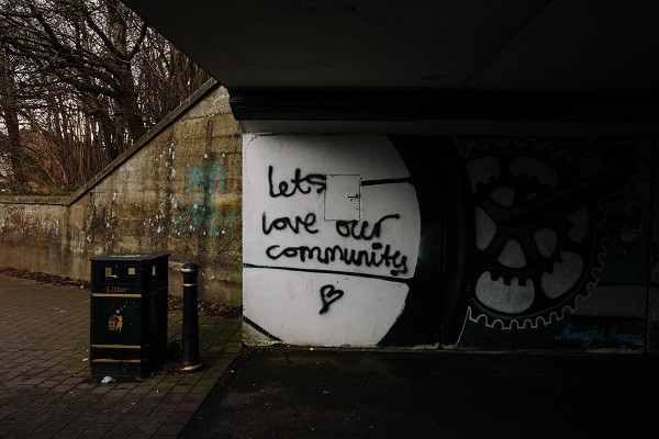 Concrete underpass with graffiti saying let's love our community