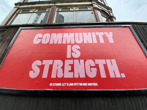 Red billboard saying community is strength